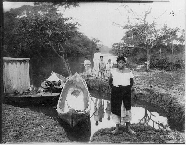 [Woman with basket on her head and 4 children standing on bank; 2 dugout boats and 2 other boats in water, 1917]