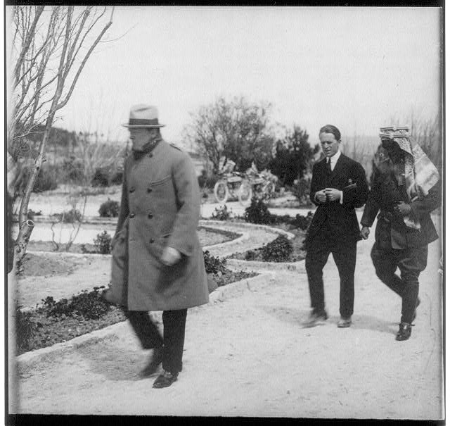 """[Winston Churchill, """"Lawrence of Arabia,"""" and Emir Abdullah walking in the gardens of the Government House, Jerusalem, during secret conference]"""