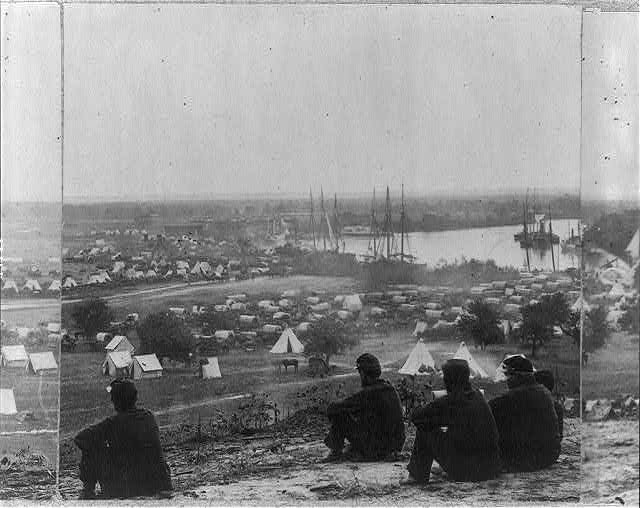 [Encampment of Army of Potomac at Cumberland Landing on Pamunkey River; 5 Union soldiers seated on hill in foregrd.]