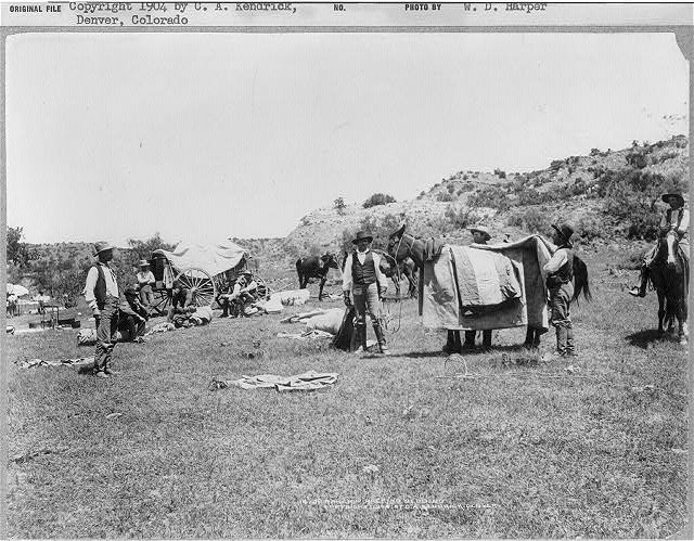 JA Ranch, Texas. 1903. JA ranch hands packing their bedding while out on the range