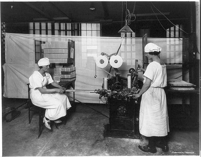 [2 women operating gum-wrapping machine at the American Chicle Company Plant]