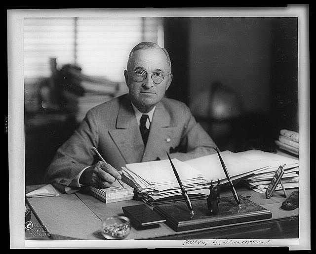 [Harry Truman, half-length portrait, seated at desk, facing front, holding pencil]