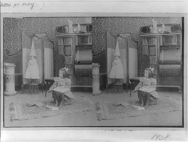 [Girl seated in middle of room with books; smaller child standing on stool and wearing dunce cap]