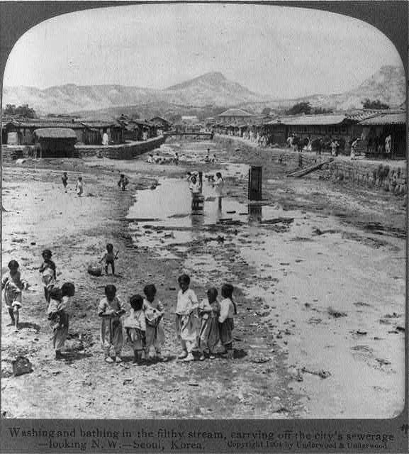 Washing and bathing in the filthy stream, carrying off the city's sewage, looking N.W., Seoul, Korea