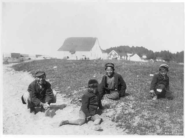 [Aleutian Islands? : 4 Indian boys seated on ground, buildings in backgrd.]