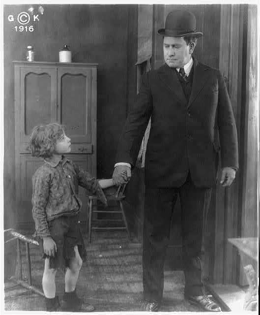 [Motion picture still showing man wearing derby and holding hand of boy wearing cutoff trousers.]