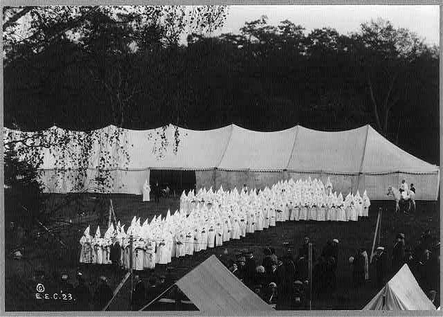 [Group of hooded Ku Klux Klan members posed in shape of a cross in front of tent]