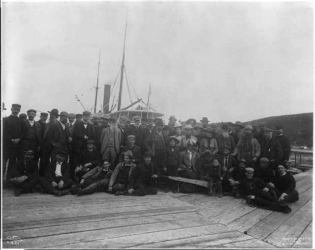 [Large group of men and women on dock in front of ship, Alaska or the Aleutian Islands]