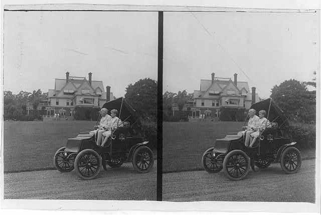 Thomas A. Edison and son(?) in automobile and large house in background