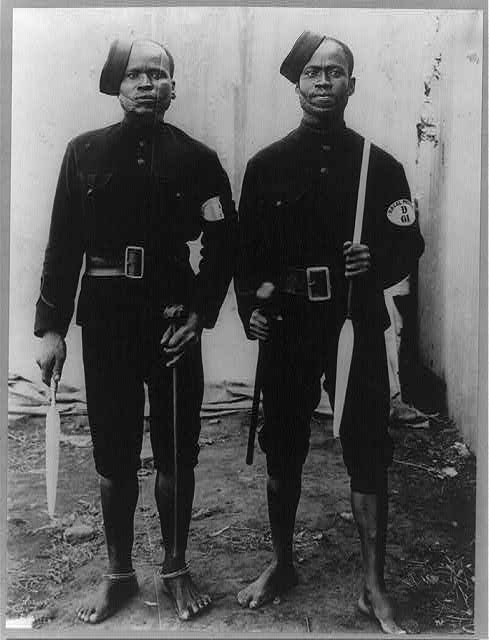 [2 barefooted policemen posed full lgth., Capetown, South Africa]
