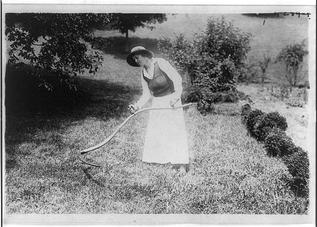 Alma Gluck cutting grass with a scythe, Aug. 3, 1917