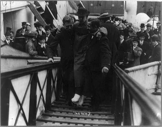 [Harold Bride, surviving wireless operator of the TITANIC, with feet bandaged, being carried up ramp of ship]
