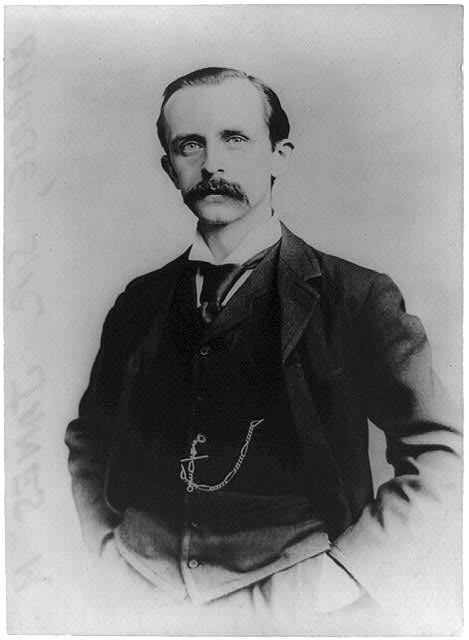 [Sir James M. Barrie, author, half-length portrait, standing, facing left, with hands in pockets]