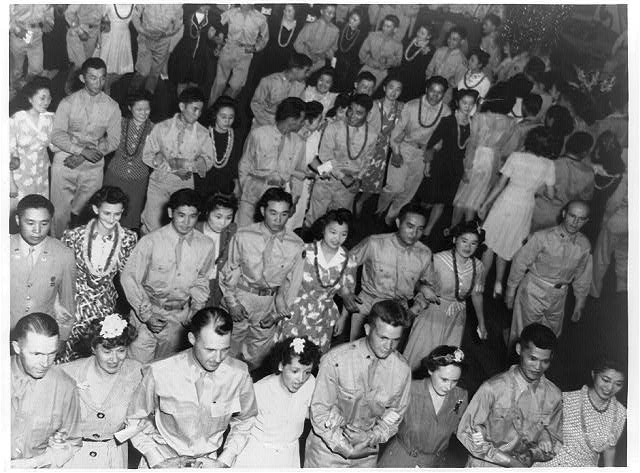 [Japanese American soldiers of the 442nd Combat Team at dance, Camp Shelby, Mississippi, with Japanese American girls from Jerome and Rohwer Relocation Center in Arkansas: March with women guests, highlighting the dance, led by their officers]