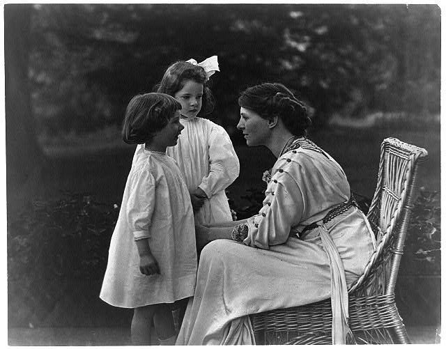 [Mrs. Frank Vanderlip seated on porch, with two children]