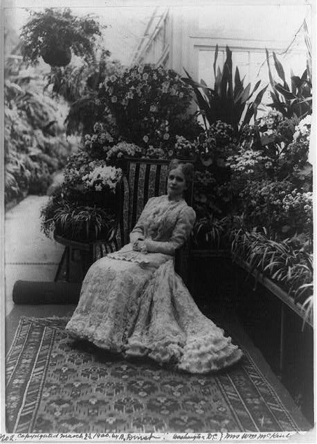 [Mrs. Ida Saxton McKinley, full-length portrait, seated, facing left; in garden(?)]