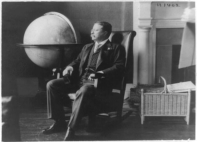 [Theodore Roosevelt, full-length portrait, seated by world globe, facing left]