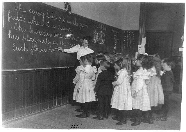 Elementary school children standing and watching teacher write at blackboard, Washington, D.C.
