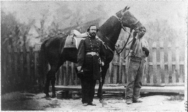 [M. Miller, Colonel, 18th Mo. Infantry, full-length portrait, facing right, standing before horse held by African-American man]