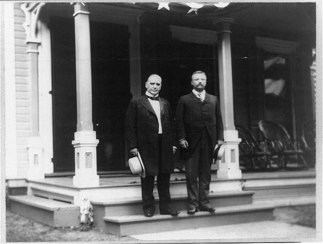 [William McKinley and Theodore Roosevelt standing on step of porch]