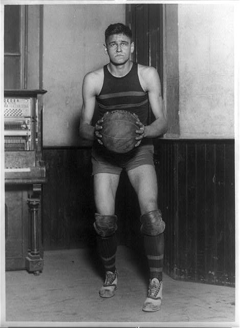 [John Loebler, center on George Washington University basketball team, standing, full-length portrait, holding basketball]