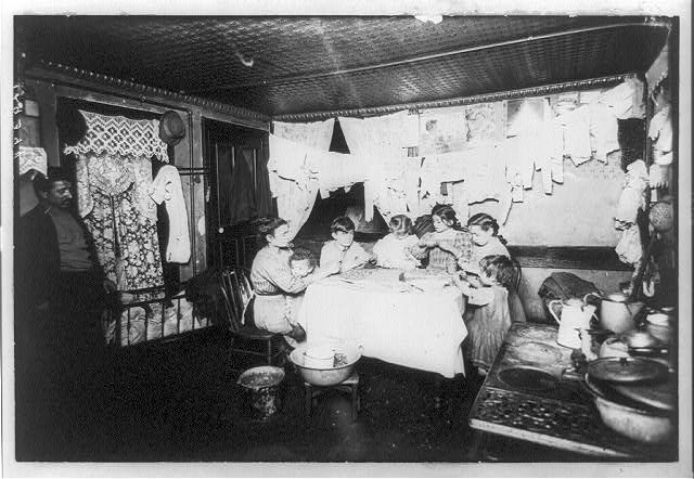 In a New York tenement house - the whole family at work taking out the pecan kernels