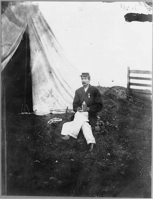 [Capt. Huff's clerk, full-length portrait, seated, facing left, in front of tent, holding book]