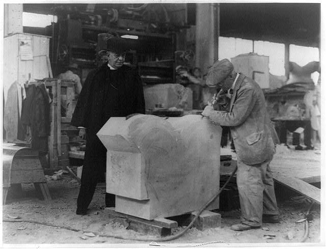 [Bishop James E. Freeman watching a stone cutter of the George A. Fuller Co. put the finishing touches on a section of the base for the National Cathedral on Mount Saint Alban]
