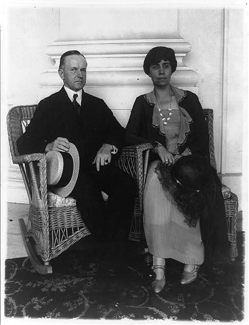 [Calvin Coolidge and his wife, full-length portrait, seated in wicker armchairs]
