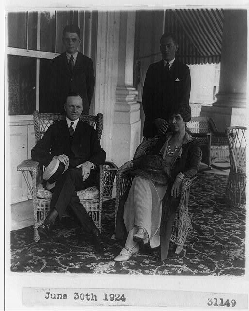 [Pres. and Mrs. Calvin Coolidge, seated, full-length, in wicker arm chairs, with two sons standing behind them]