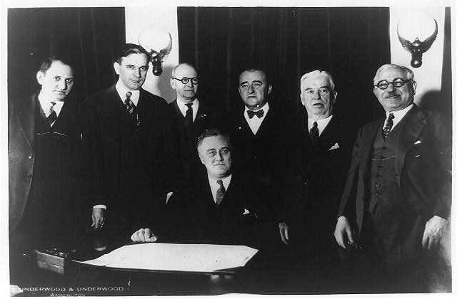 [President Franklin Roosevelt and six other men in cabinet room]