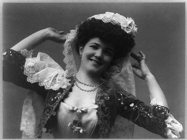 [Emma Trentini, half-length portrait in costume, facing front, hands raised]