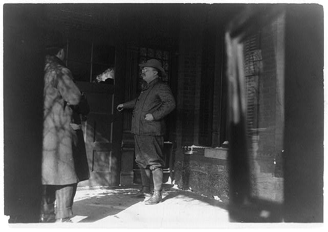 [Theodore Roosevelt, full-length, standing, facing left, opening door]