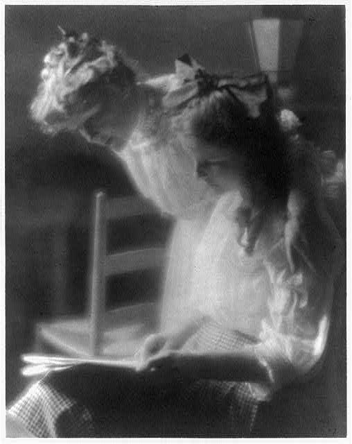 [Agnes Lee, standing, with arm around older daughter, (Agnes Lee), seated, reading newspaper(?) on lap]