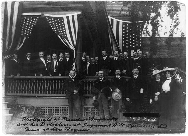[President Roosevelt and his detectives at Sagamore Hill, Oyster Bay, L.I., posed on porch with flags]