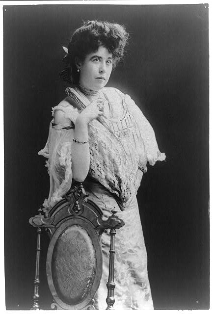 "[Mrs. James J. ""Molly"" Brown, survivor of the Titanic, three-quarter length portrait, standing, facing right, right arm on back of chair]"