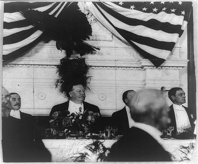 [President Taft at dinner, with eagle and U.S. flag behind him]