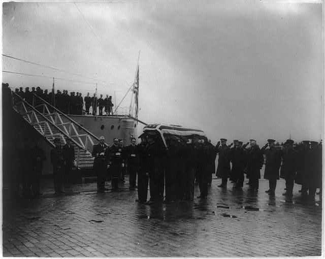 [Military funerals at Arlington National Cemetery--flag-draped casket, unloaded from ship, being carried by sailors and marines]