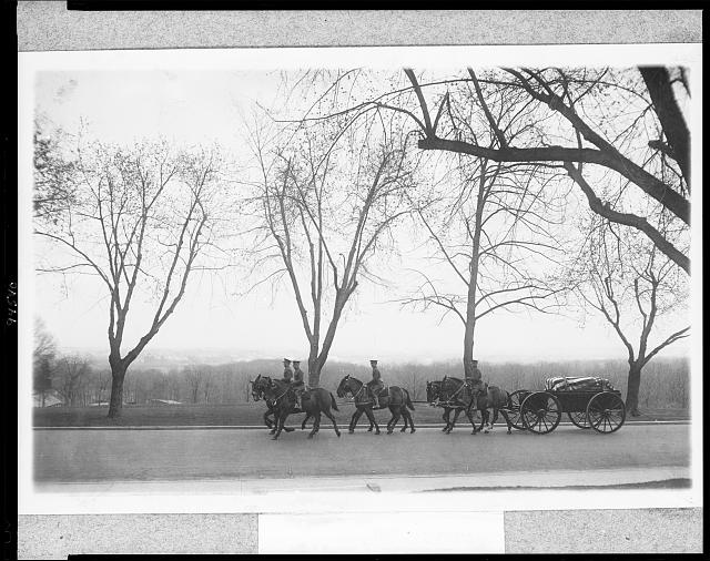 [Military funerals at Arlington National Cemetery--men on six horses pulling casket on wagon]