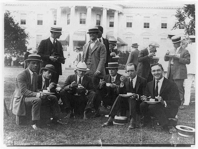 [White House photographers eating on lawn of the White House]