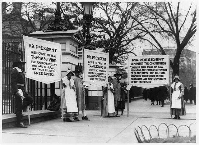 [People dressed as pilgrims carrying three signs for amnesty for political prisoners standing in front of the White House]