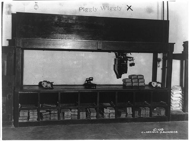 [Interior view of a Piggly Wiggly self-service grocery store showing scales on top of counter and paper bags stored under counter]
