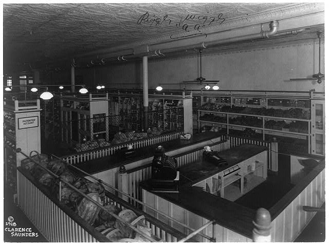 [Interior view of a Piggly Wiggly self-service grocery store showing check out counter with cash registers]