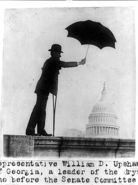 [Representative William D. Upshaw of Georgia, a leader of the drys, standing on railing with crutch and holding umbrella, with dome of the U.S. Capitol under the umbrella