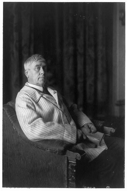 [Maurice Maeterlinck, three-quarter-length portrait, seated facing right, with open book in hands]