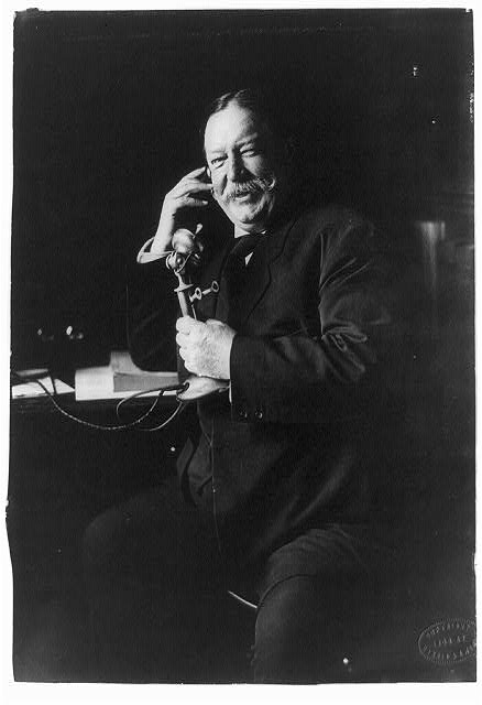 [William Howard Taft, three-quarter-length portrait, seated facing left, on telephone]