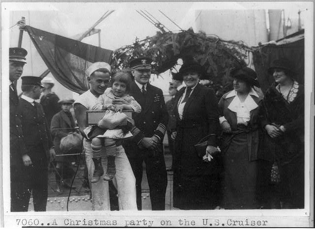 [Two orphans with Near East Relief workers and sailors on board the U.S. cruiser Pittsburgh as guests of the officers for a Christmas party in the Bosporus]