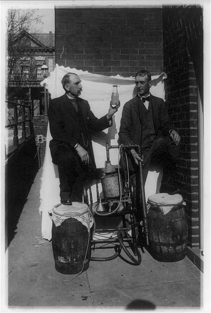 [Two men standing outdoors with small still, one of them holding up bottle of liquor]