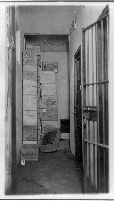 [Cases of confiscated(?) liquor stacked in corner of room with barred doors]