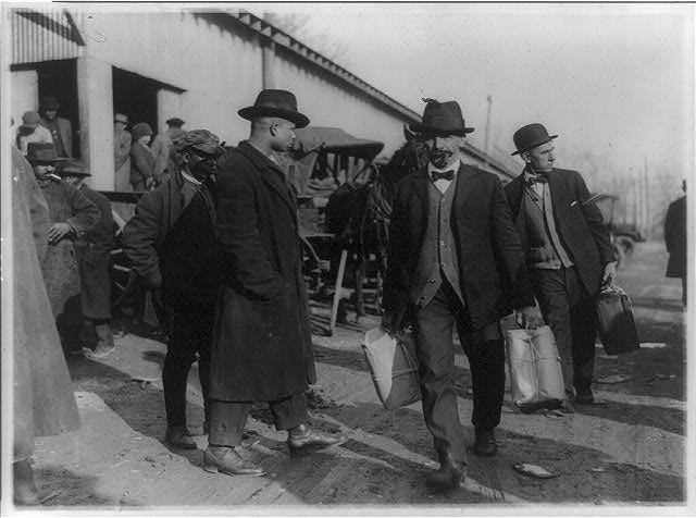 [Two men of the U.S. Internal Revenue Bureau(?) carrying packages of confiscated liquor(?) past two black men]